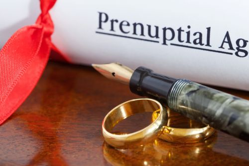 Prenuptial agreement papers with wedding bands - BartonWood
