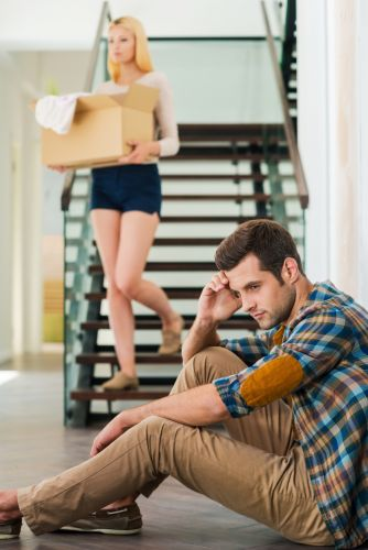 Frustrated young man sitting on the floor of his apartment while his girlfriend is leaving with boxes - BartonWood