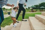 Baby walking with help of parents
